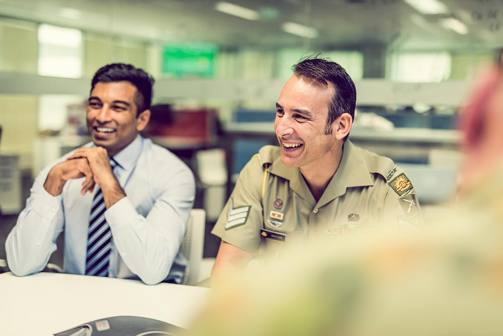 DHA staff member and Defence personnel member sitting smiling at an office desk